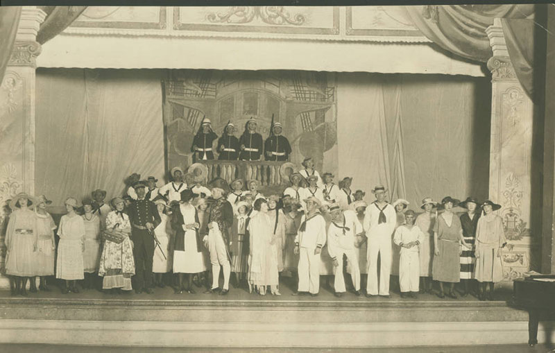 Black-and-white photo of cast members on stage.