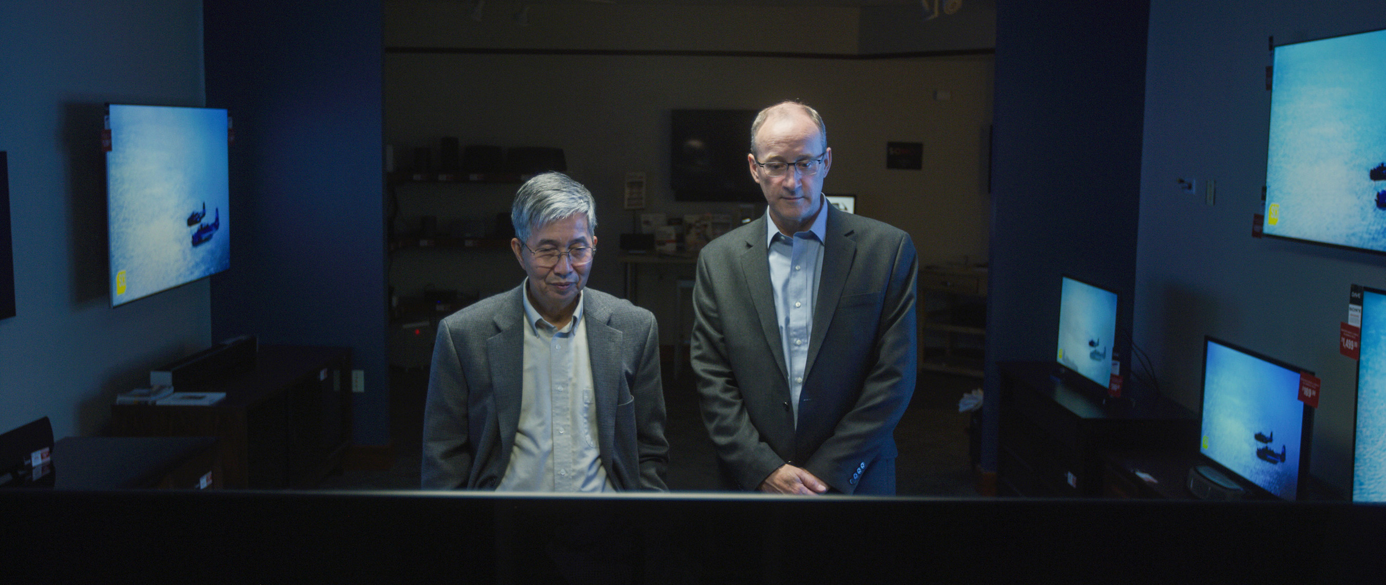 Two men stand in a darkened room surrounded by OLED monitors.