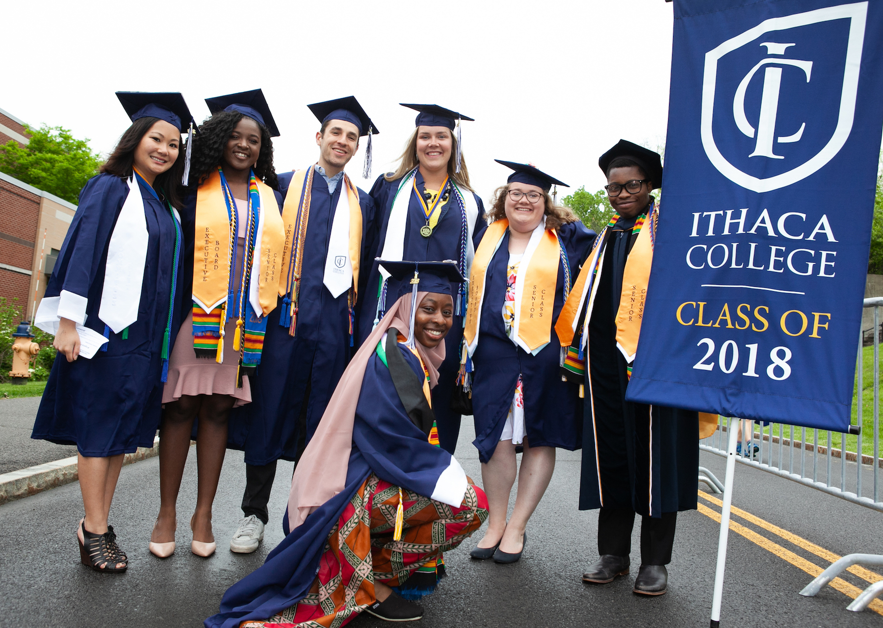 A diverse group of male and female graduates poses with a Class of 2018 banner.