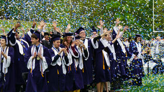 Students in caps and gowns celebrate with confetti
