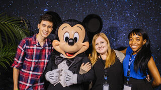 Three alumni pose with Mickey Mouse at the LA Event