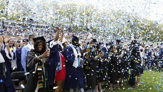 Graduates in caps and gowns celebrate with confetti
