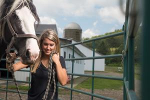 Close photo of Kendra Hubal standing next to horse, barn in background