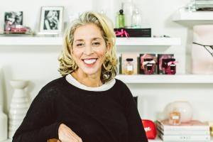 Photographic portrait of Jan Singer smiling in Victoria's Secret office