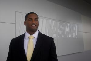 Photo portrait of Jusan Hamilton in front of NASCAR sign