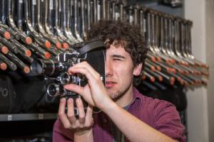 Tyler Macri looks into camera while adjusting lens