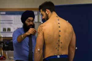 Rumit Singh Kakar attaches spherical markers to running study participant