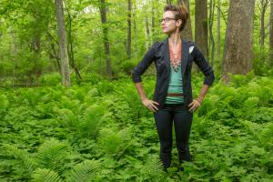 Sarah Brylinsky stands in a lush green forest