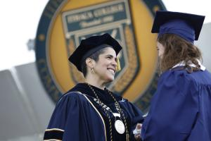 A woman in academic regalia greets a female in cap and gown during a graduation ceremony.