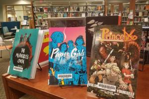 three graphic novels on display on a shelf