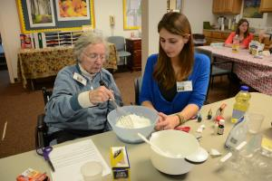 There are two individuals seated at a table. One is an elderly individual and the other is a student. The student is helping the elderly individual with mixing together recipe ingredients.