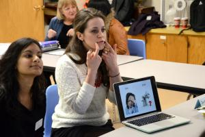 "Two students are working with a client. There is a laptop computer that indicates facial expressions and the difference between the word ""sick"" and ""seek."" One student in a white sweater has her hands to her face, showing the client how to move their mouth properly to make the sounds distinctly."