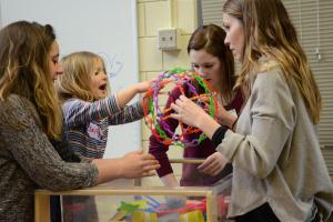 Three students are supervising a young child playing with a brightly colored toy that is being pulled out of a box.