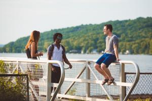 Three students are on a dock at Cayuga Lake. Two students are standing and one is sitting on the railing. It is a beautiful sunny day.