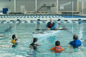 There are five people in a swimming pool. One is a man in a kyak who is speaking with four students that are in the pool water wearing life jackets