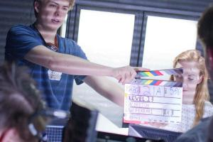 Student holds a clapperboard on set prior to a scene being filmed.