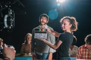 Student holds a film clapperboard in front of an actor prior to a scene.