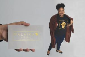 "A hand holds a business card that reads ""Malaika Apparel,"" while a young woman poses in the background."