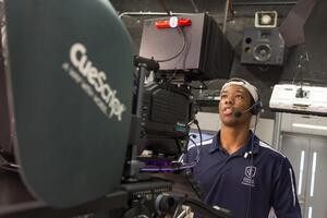 Student wearing a headset looks into a viewfinder while operating a camera on set.