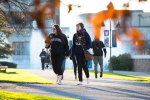 Students walk across campus during autumn.