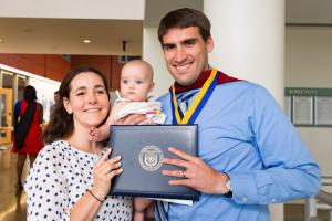 graduate with diploma, wife, and baby