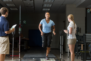 A student in a blue shirt is running on a sensor pad with sensors attached to her legs. Another student is standing nearby taking notes on a clipboard.