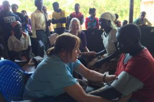 Mary Taylor taking a young man's blood pressure in Malawi.