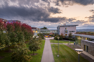 View of IC Campus overlooking path to buildings against a sunset and clouds backdrop.