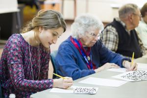 student working along side two older adults