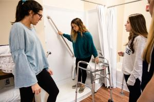 "Two students are standing watching a third student in a ""mock"" shower, using grab bars and other assistive devices to mimic a client taking a shower."