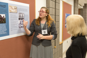 A student standing at a research poster presenting her research to a person in a hallway