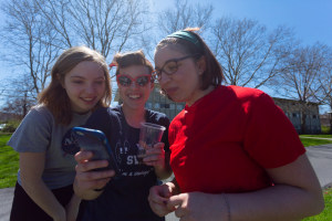 3 Honors students stand outside in the sun, looking at a photo on a student's phone.