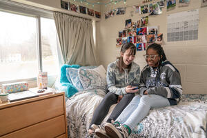 two students sitting on a bed near a window in a dorm room