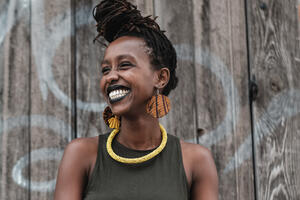 A picture of a young, smiling Black woman.  Her hair is pulled into a front knot at the top of her forehead.  She is wearing a dark green tank top, dangling, round, wooden earrings and a yellow beaded necklace.  She is looking off to her right.  Behind her is a brown wooden fence with some white writing on it.