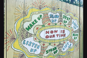 "A mural painted on a light yellow fence.  The middle is a oval that reads ""Now is our time"" and is surrounded by bubbles that read, ""wake up"", ""slow up"", ""step up"", ""show up"", ""rise up"", ""lift up"", ""speak up"", and ""listen up"".  The outsides of the mural are decorated with sprays of dots and borders in white, yellow, and red."