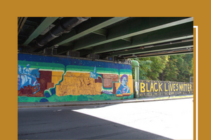 "A picture of an underpass with a mural on the far side wall.  The mural has a picture of Fredrick Douglass as well as the words ""Black Lives Matter"""