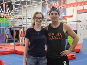 Amy Jacobson poses with Drew Drechsel in the gym as people train on obstacles in the background.