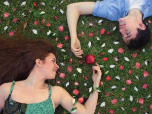 Actors from 'The Diary of Adam and Eve' lay on grass peering at each other. Flower pedals cover the ground and an apple is between their hands.