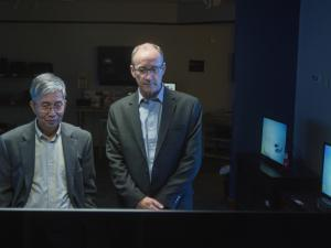 Chin Wan Tang and Steven Van Slyke stand in a darkened room surrounded by OLED monitors.
