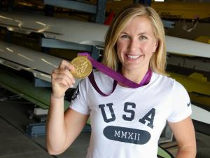 Meghan Musnicki holds up the Olympic gold medal around her neck while standing in a boathouse.