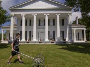 A man pushes a rolling machine in front of a white, Greek Revival style mansion