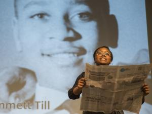 A young black woman in the foreground holds a newspaper while a photo of Emmett Till is projected on screen behind her.