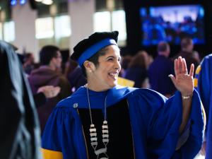 A woman in ceremonial academic cap and robes smiles and waves.