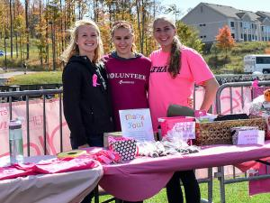 Three young women stand together and smile while standing outdoors at a table covered in raffle prizes.