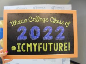 "Handheld chalkboard that reads ""Ithaca College Class of 2022 #icmyfututre!"""