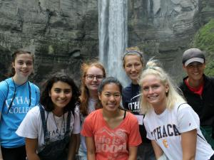 A group of young people in front of a waterfall