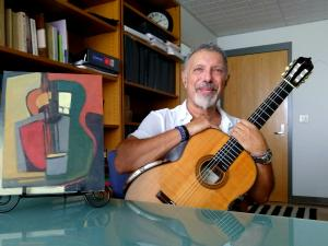A man posing with a guitar and an abstract painting