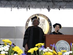 Two women on stage in academic regalia