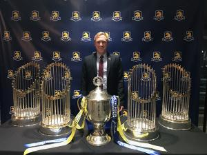Man standing behind Boston Marathon trophy and world series trophies