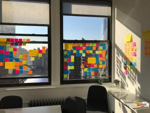 Sunlight shining through a window covered in multiple colors of post-it notes.